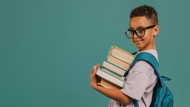 Ragazzo di scuola di vista laterale che tiene una pila di libri copia spazio Foto Premium