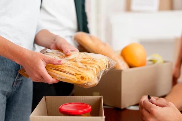 Vista laterale del volontario che prepara la scatola di donazione con il cibo Foto Premium