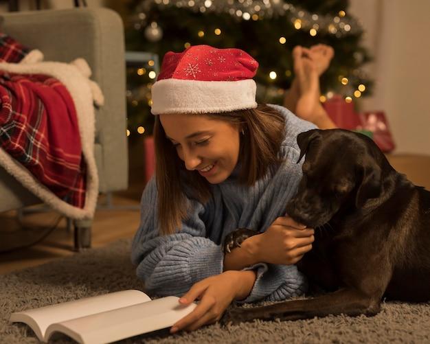 Vista laterale della donna sul libro di lettura di natale con il suo cane Foto Premium