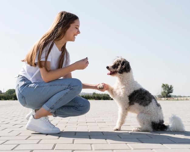 Vista laterale della donna che tiene la zampa del cane Foto Premium