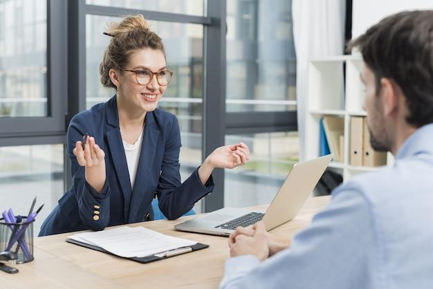 Vista laterale della donna che tiene un colloquio di lavoro con l'uomo Foto Premium