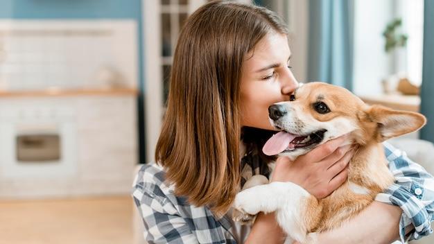 Vista laterale della donna che tiene e che bacia il suo cane Foto Premium
