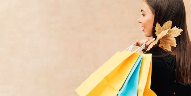 Donna di vista laterale che tiene i sacchetti della spesa con lo spazio della copia Foto Premium