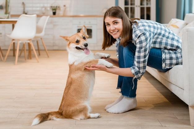 Vista laterale della donna che posa mentre tenendo le zampe del cane Foto Premium