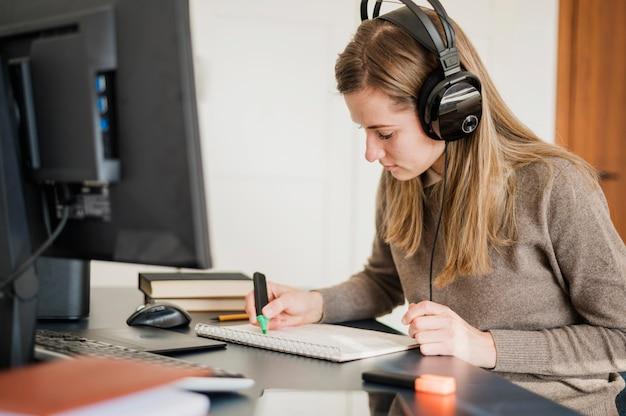 Vista laterale della donna con le cuffie allo scrittorio che partecipa alla classe online Foto Premium