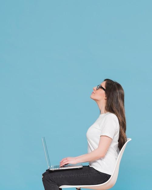 Donna di vista laterale con il computer portatile in grembo Foto Premium