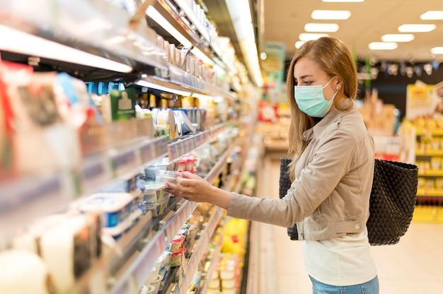 Donna di vista laterale con la maschera ad acquisto di drogheria Foto Premium
