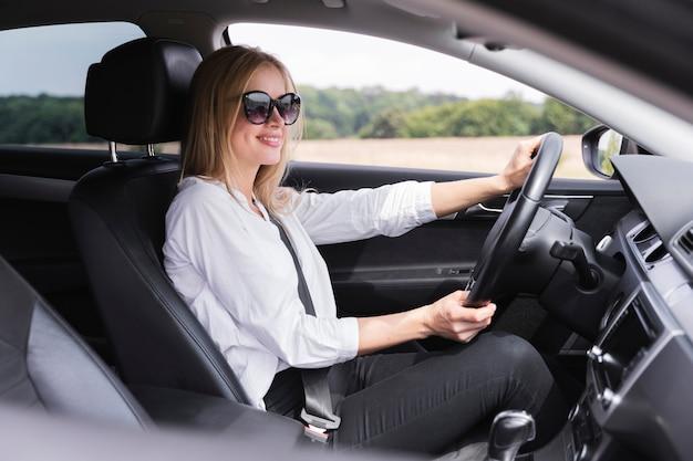 Vista laterale della donna con la guida di occhiali da sole Foto Premium