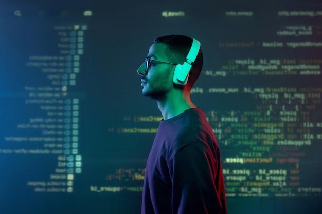 Vista laterale del giovane programmatore in cuffie e abbigliamento casual in piedi contro lo schermo con informazioni decodificate Foto Premium