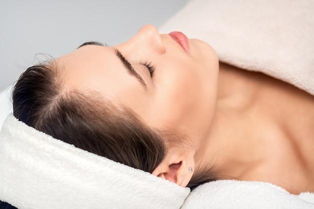 Vista laterale della giovane donna sdraiata sul tavolo estetista con gli occhi chiusi durante l'attesa per la procedura cosmetica nel salone di bellezza Foto Premium