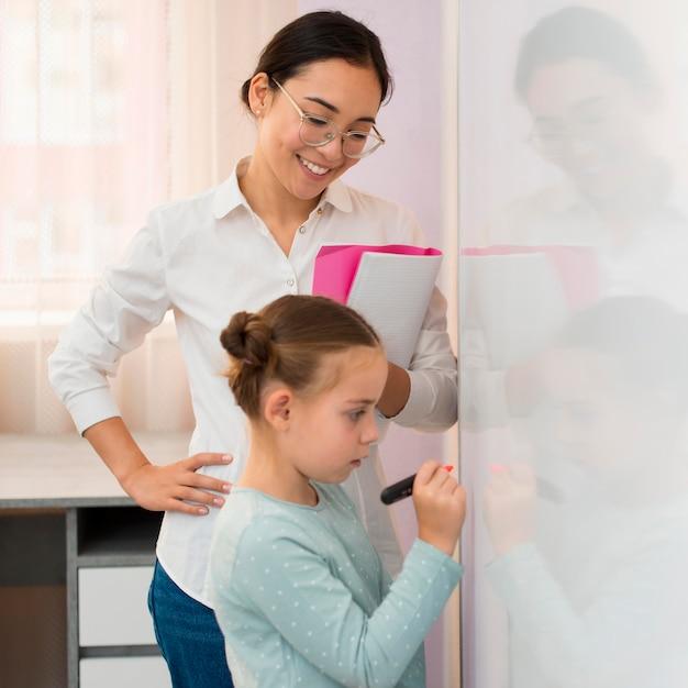 Bambina di lato che scrive su una lavagna bianca accanto al suo insegnante Foto Premium