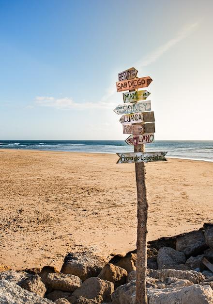 Segno sulla spiaggia che indica diversi paesi al tramonto Foto Premium