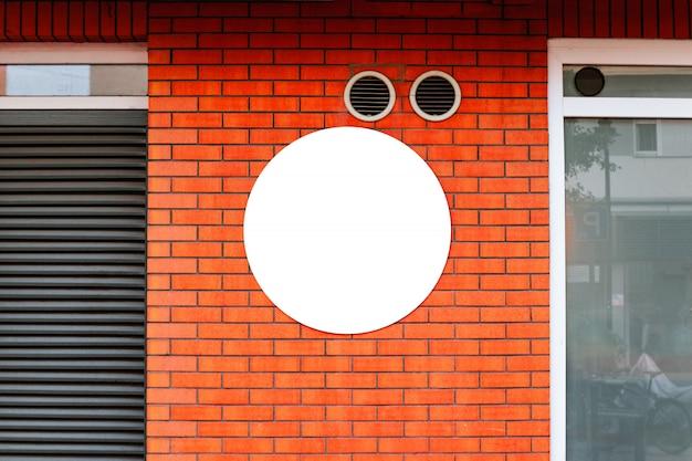 Modello del cerchio di progettazione di logo della disposizione del deposito dell'insegna sul muro di mattoni rosso. Foto Premium
