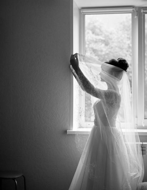 Sagoma della sposa aspettando lo sposo. ritratto in bianco e nero di una sposa elegante in piedi davanti a una finestra Foto Premium