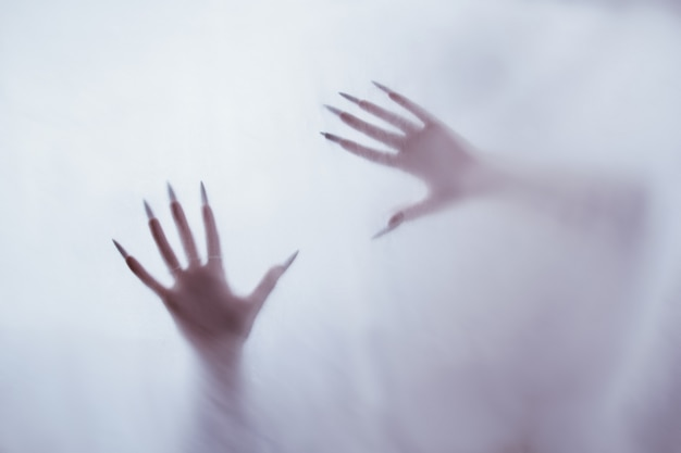 Silhouette di una figura sessuale femminile dietro un vetro nebbioso. concetto dello spirito di poltergeist dall'altro mondo. spaventose mani della morte attraverso il tessuto. Foto Premium