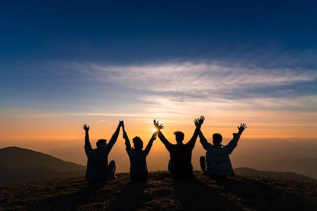 Silhouette di amici si stringono la mano e seduti insieme nella felicità del tramonto Foto Premium