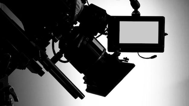 Immagini della sagoma della videocamera nella produzione di uno studio commerciale televisivo che opera o riprende dal cameraman e dalla troupe cinematografica sul set e sul sostegno su gru professionale e treppiede per un facile utilizzo Foto Premium