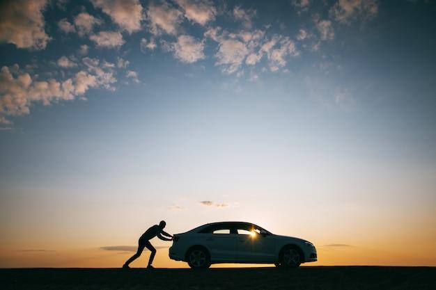 Siluetta dell'autista dell'uomo che spinge la sua automobile dopo la ripartizione al tramonto Foto Premium