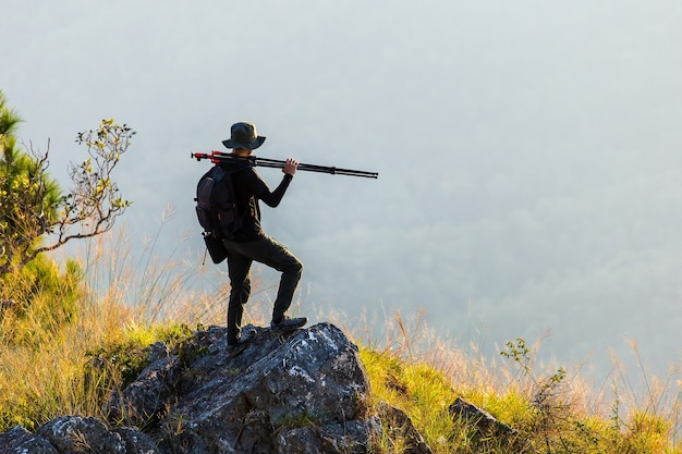 Sagoma di uomo alza le mani sulla cima della montagna Foto Premium