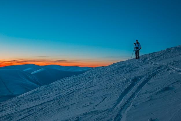 Siluetta del fotografo dell'uomo che sta sulla collina e che fa foto della valle e delle montagne di sera al tramonto variopinto rosa. Foto Premium