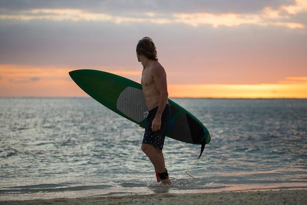 Surfista di bordo di pagaia della siluetta sul tramonto Foto Premium