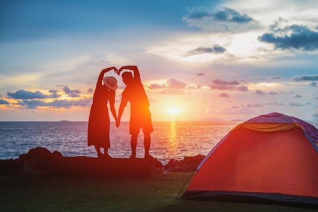 La silhouette degli sposi che si tengono per mano a forma di cuore sulla spiaggia del mare al tramonto Foto Premium