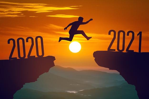 Sagoma di giovane uomo che salta tra il 2020 e il 2021 anni con il tramonto Foto Premium