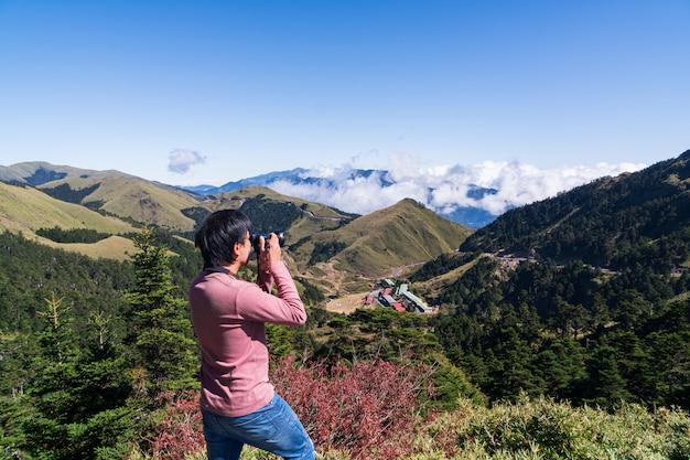 La siluetta del giovane in maglietta rosa a maniche lunghe che gode della vista stupefacente e prende una foto in cima alla montagna Foto Premium