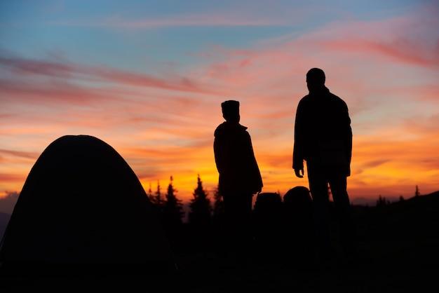 Sagome di un uomo e una donna in piedi vicino alla loro tenda sulla cima di una montagna tramonto mozzafiato Foto Premium