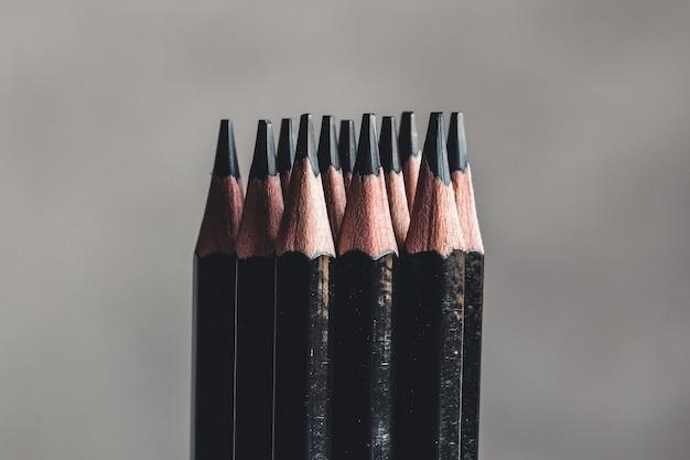 Matite di grafite semplici su sfondo grigio. matite nere, spazio per il testo Foto Premium