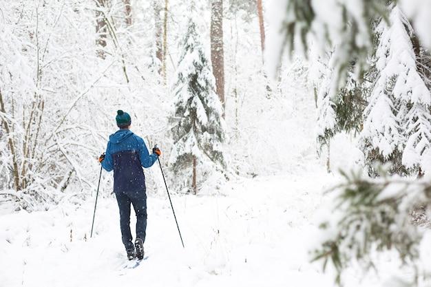 Sciatore in cappello con pompon con bastoncini da sci in un bosco innevato. sci di fondo Foto Premium