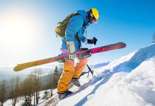 Sciatore sul pendio in montagna in giornata invernale Foto Premium