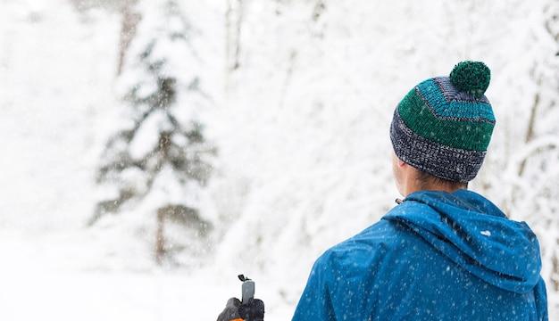 Sciatore in giacca a vento e cappello con pompon con bastoncini da sci in mano con la schiena su un bosco innevato. sci di fondo nella foresta invernale, sport all'aria aperta, stile di vita sano. Foto Premium