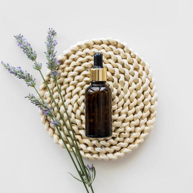 Olio per la pelle e fiori vista dall'alto Foto Premium