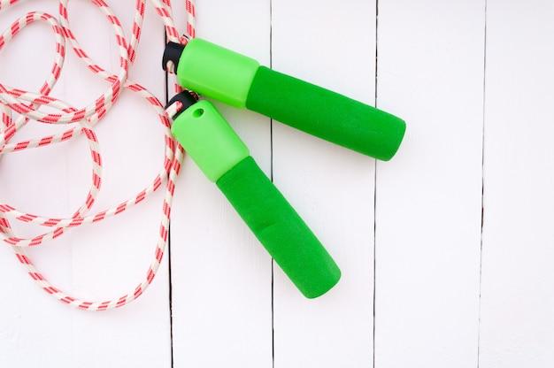 Salto della corda su un fondo di legno bianco Foto Premium