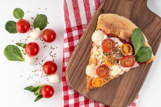 Fetta di pizza deliziosa sul bordo di legno Foto Premium