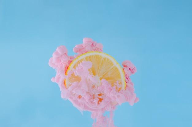Affetti il limone con il fuoco parziale di dissoluzione del colore rosa del manifesto in acqua su fondo blu. Foto Premium