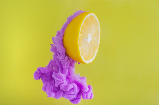 Affetti il limone con il fuoco parziale di dissoluzione del colore viola del manifesto in acqua su fondo giallo. Foto Premium