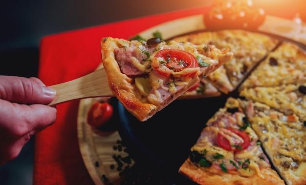 Una fetta di pizza in mano. un ristorante. Foto Premium
