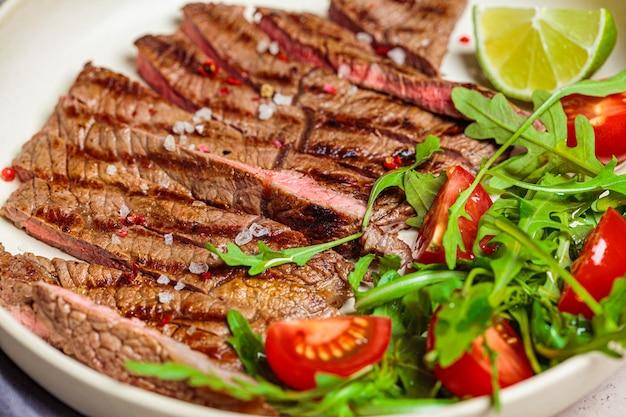 Fette di bistecca di manzo alla griglia con rucola e insalata di pomodori nel piatto bianco, sfondo scuro, close-up. Foto Premium