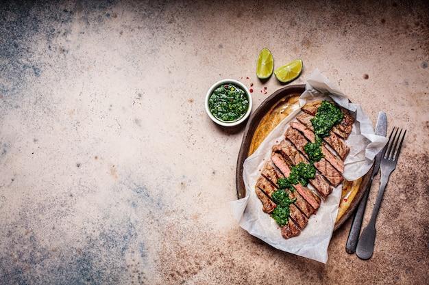 Fette di bistecca di manzo alla griglia con salsa chimichurri sul piatto scuro, vista dall'alto, sfondo scuro. Foto Premium