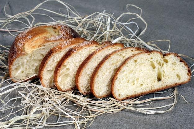 Fette di pane bianco che giace nella paglia sulla tovaglia di lino grigio Foto Premium