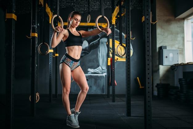 Esercizio di atleta femminile sottile su anelli di ginnastica Foto Premium