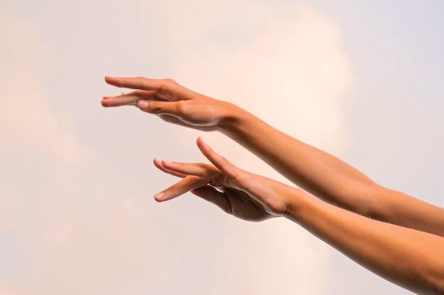 Mani femminili sottili contro il cielo ballando balletto Foto Premium