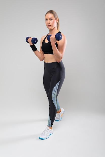 Ragazza bionda slim fit in un'uniforme sportiva impegnata in esercizi fisici Foto Premium