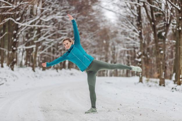 Sportiva sottile facendo esercizi di riscaldamento in natura in caso di neve. freddo, sport invernali, vita sana, inverno Foto Premium