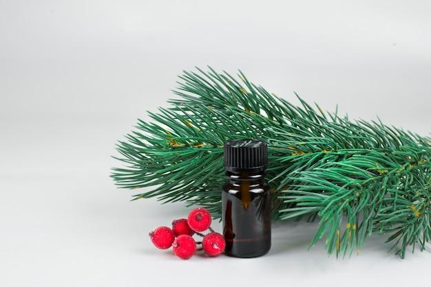 Piccola bottiglia cosmetica marrone con rami di albero di natale e roba natalizia rossa su sfondo chiaro Foto Premium