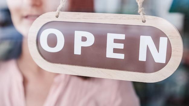 Apertura di piccole imprese. ruotando il segno da vicino ad aperto. persona irriconoscibile Foto Premium