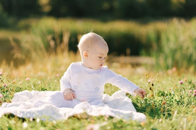 Il bambino piccolo si siede su una coperta sulla riva del lago all'aperto. l'estate cammina con il tuo bambino Foto Premium