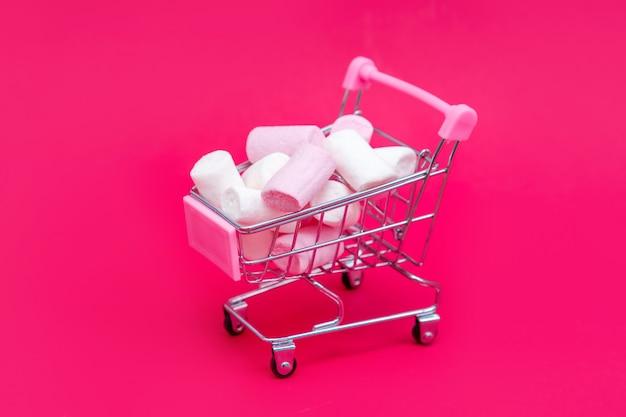 Piccolo carrello della spesa pieno di dolci caramelle marshmallow. fai regali con amore a san valentino Foto Premium